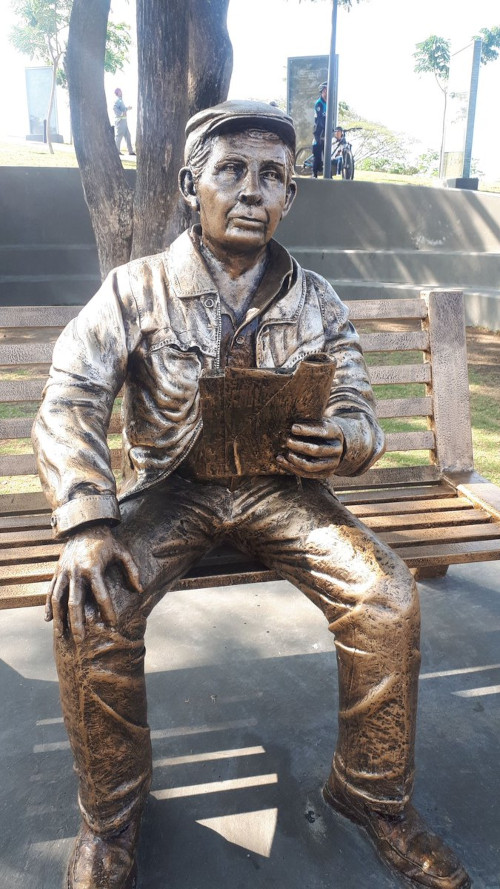 Statue of Horacio Hidrovo Peñaherrera sitting on a bench.